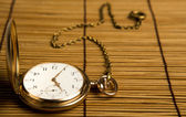Gold pocket watch on bamboo rugs — Stock Photo