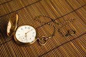 Gold pocket watch on bamboo rugs — ストック写真