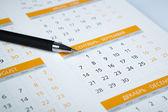 Black pen lying on the calendar — Stock Photo