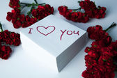 Notebook with marker inscription I love you and roses — Stock Photo