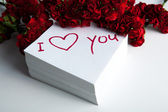 Notebook with marker inscription I love you and roses — Stok fotoğraf