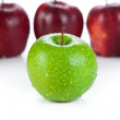 Maroon apples lined up in a row and green apple closeup — Stock Photo #41754721