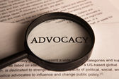 Document with the title of advocacy under a magnifying glass — Stock Photo