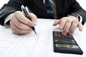 Businessman holding a pen and counts the budget — Foto Stock