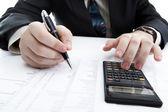 Businessman holding a pen and counts the budget — Foto de Stock