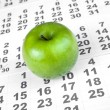 Green apple on sheets of wall calendar — Stock Photo