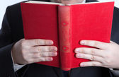 Man holding an open red book — Stock Photo