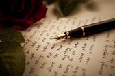 Fountain pen on text sheet paper with rose — Photo