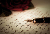 Fountain pen on text sheet paper with rose — Stok fotoğraf