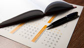 Wall calendar with pen and diary closeup — Stock Photo