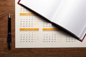 Wall calendar with pen and diary closeup — Stock Photo