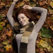 Beautiful young woman laying in fallen leaves. - Stock Photo