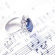 Brightly jewelled ring on sheet music - Foto Stock