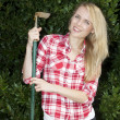 Beautful young woman with gardening hoe - Stok fotoğraf