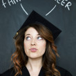Woman in graduation gown infront of chalk board - Stock Photo
