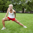 Beautiful female exercising in park - Stock Photo