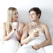 Happy young couple in bed - Foto Stock