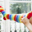 Pulling on stripy leggings. - Stock Photo