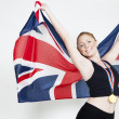 Attractive redhead woman holding up a Union Jack flag - Stock Photo