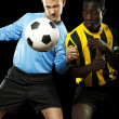 Soccer players challenging for the ball - Stock Photo
