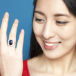 Beautiful Asian girl with jewelled ring - Stock Photo