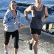 Happy and active young couple jogging beside sea - Stock Photo