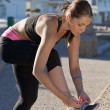 Young woman in sportswear, tying her shoelace on embankment - Foto Stock
