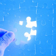 Royalty-Free Stock Photo: Human hand embed missing jigsaw puzzle piece into place