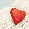 Red heart shape candy on musical notes - Stock Photo