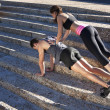 Fit young man doing push ups on steps with his girlfriend on his back - Stockfoto