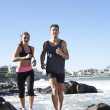 Royalty-Free Stock Photo: Happy and active young couple jogging along seashore