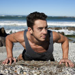 Royalty-Free Stock Photo: Muscular man doing push ups at seashore against blue sky