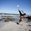 Fit young woman in upside down yoga pose at seashore - Stock Photo