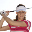 Confident female golfer taking a shot - Stock Photo