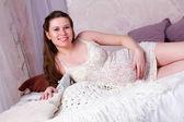 怀孕的女人躺在床上微笑 — 图库照片