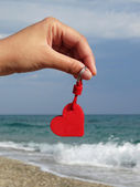 Heart pendant at the beach — Stock Photo