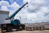 Automobile crane with risen telescopic boom outdoors over blue s — Stock Photo