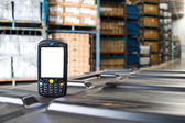 Bluetooth barcode scanner in front of modern warehouse  — Stock Photo