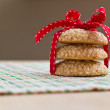 Royalty-Free Stock Photo: Freshly made sesame seed cookies stacked and tied with red striped ribbon