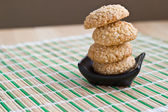Freshly made sesame seed cookies stacked on black plate — Stock Photo