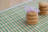 Freshly made sesame seed cookies stacked and tied with ribbon on bamboo mat — Stock Photo