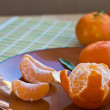 Peeled tangerine with segments on plate — Stock Photo