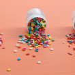 Colorful sugar sprinkles scattered on a wooden table - Stock Photo