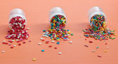 Colorful sugar sprinkles scattered on a wooden table — Stock Photo