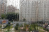 Drops of rain on glass against city background, shallow DOF — Stock Photo