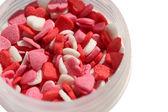 Herzförmige zucker streuseln in flasche isoliert auf weißem hintergrund — Stockfoto