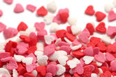 Colorful sugar sprinkles scattered on white background — Stock Photo