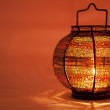 Small decorative lamp with a candle on orange background - Stock Photo