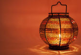 Small decorative lamp with a candle on orange background — Stock Photo