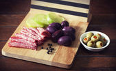 Slices of salami and black and green olives — Stock Photo